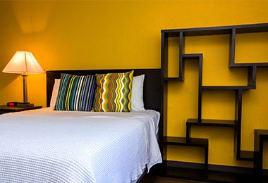 Furnished studio apartments with night stand, lamp, queen bed and bookshelf.