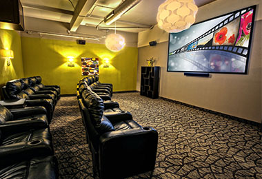 Movie theater room with large projection screen and black leather chairs.