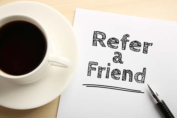 "Coffee cup with a piece of paper next to it that says ""Refer a Friend""."